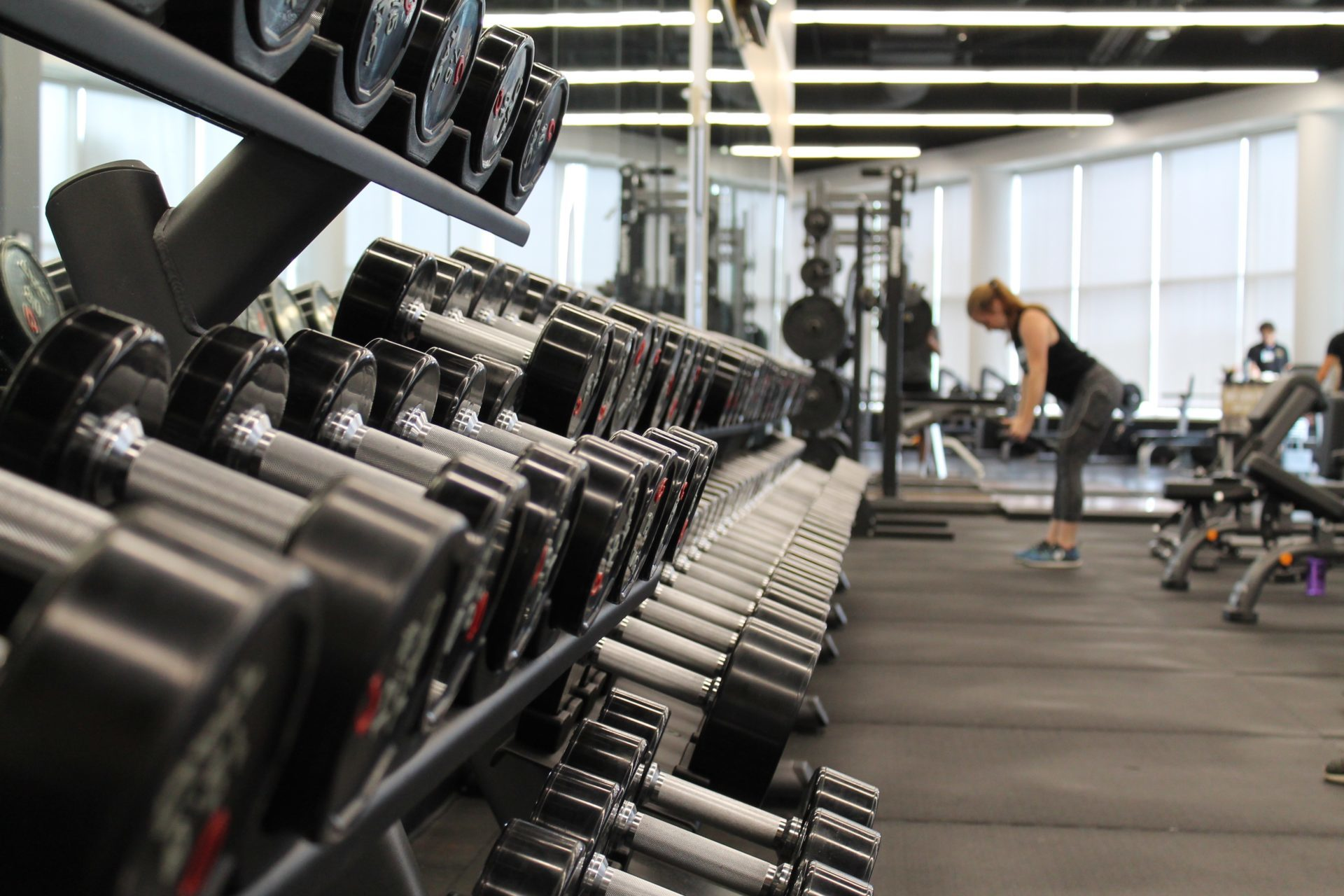 person working out in a gym, dumbbells